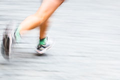 Motion blurred runner's feet in a city environment stock photography