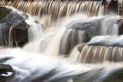 Motion blurred stream falling over a weir. A small moorland stream cascading over a weir captured using a slow shutter speed to blur the movement of the water Stock Photography