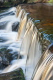Motion blurred stream falling over a weir. A small moorland stream cascading over a weir captured using a slow shutter speed to blur the movement of the water Royalty Free Stock Photography
