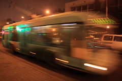 Motion blurred trolleybus. The movement of the trolleybus with the motion blur on the street in the evening stock photos