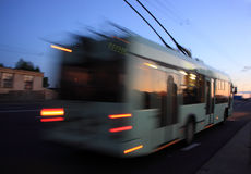 Motion blurred trolleybus. Movement of a blurred trolleybus in the city at dusk royalty free stock photography