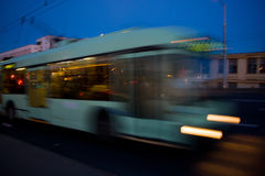 Motion blurred trolleybus. Movement of a blurred trolleybus in the city at dusk royalty free stock photo