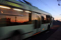 Motion blurred trolleybus. Movement of a blurred trolleybus in the city at dusk stock image