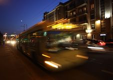 Motion blurred trolleybus. The motion of a blurred trolleybus in the street in the evening royalty free stock photography
