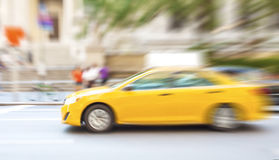 Motion blurred yellow taxi on a city street Stock Photo