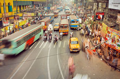 Motion blurs from public buses, cars and rushing people on indian road with many stores Royalty Free Stock Photo