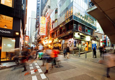 Motion blurs of rushing people on streets with tall glass and concrete buildings in busy district of  city. HONG KONG, CHINA - FEB 12: Motion blurs of rushing Stock Photography
