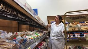 Motion of bread clerk stocking bread for sale inside Superstore. In BC Canada stock video footage