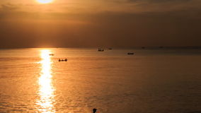 Motion from Bright Sun Path Boats to Silhouette in Sea at Sunset. Panorama from bright sun on skyline sun path on water distant boats to silhouette with rod in stock video footage