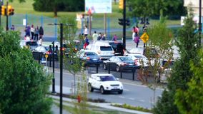 Motion of busy traffic flow and people walking into park for Canada day event stock footage