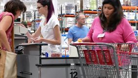 Motion of cashier scanning food and stocking them on trolley at check out counter. Inside Costco stock video