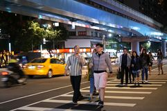 Motion of commuters crossing street to take bus or skytrain. In Taipei Taiwan Stock Photo