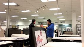 Motion of customer shopping mattress and discussing with clerk. Inside Sears store stock footage