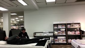 Motion of customer shopping mattress and discussing with clerk. Inside Sears store stock video