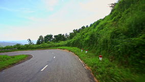 Motion down Country Curvy Road among Hilly Landscape under Sky stock video footage