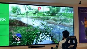 Motion of father and children playing Xbox car racing game on tv screen at Microsoft store. With 4k resolution stock video footage
