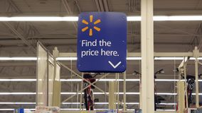Motion of find the price here sign. Inside Walmart store stock video footage