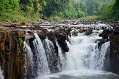 Motion and flowing water of Tad Pha Suam waterfall Stock Images