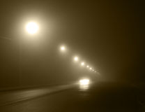 Motion in fog. An automobile moving on the road with lanterns in strong fog Stock Photos