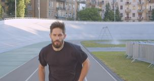 Motion front view portrait of adult caucasian sporty male runner jogging on the stadium in the urban city outdoors.  stock footage