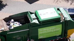 Motion of garbage truck collecting garbage. And leaving the apartment stock video footage