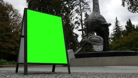 Motion of green screen sign beside Vancouver aquarium totem stock video footage