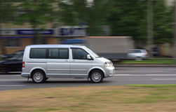 Motion grey blurred minibus. Motion blurred grey minibus on the street in the afternoon royalty free stock photography