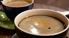 Motion of hot coffee with bubbles on table and reflection with people walking through. Inside coffee shop stock video footage