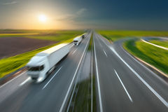 Motion image of modern delivery trucks on the highway. Three new trucks in a row driving fast towards the sun. Speed blurred motion drive on the freeway. Freight Stock Image