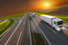 Motion image of new delivery trucks on the highway. Three new reefer trucks in a row at left side driving on freeway with speed blurred motion. Freight scene on Royalty Free Stock Photos