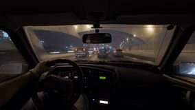 Motion lapse shot of male driver is sitting holding steering wheel in car, riding in night city. Winter season stock video footage