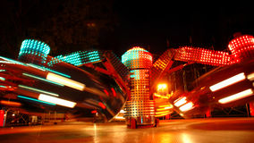 Motion of lights. Terrific speed of carousel in evening park Royalty Free Stock Photo