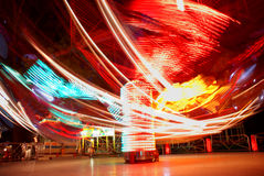Motion of lights. Terrific speed of carousel in evening park Royalty Free Stock Images