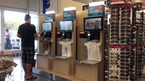 Motion of man paying milk at self-check out counter. Inside shopper drug mart store stock footage