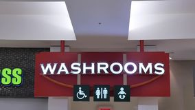 Motion of man and woman washroom logo on wall. Inside Coquitlam shopping mall stock video