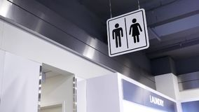 Motion of man and woman washroom logo beside wall. Inside shopping mall stock video