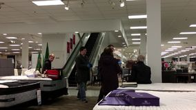 Motion of medical team helping injured shopper and sitting on mattress. Inside Sears store stock video