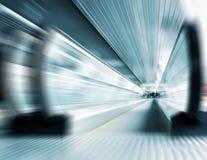 Motion metro escalator. Abstract composition of motion metro escalator in glass corridor royalty free stock photos