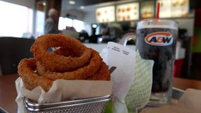Motion of onion rings and root beer on table stock video
