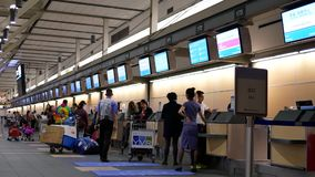 Motion of passengers with luggage at check in area stock footage