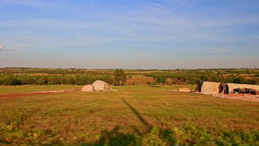 Motion Past Sunny Rural Landscape with Farmer Buildings stock footage