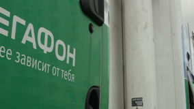 Motion Past Truck with Logo Megafon on Cabin Door. KAZAN, TATARSTAN/RUSSIA - MAY 15 2013: Motion past green and white truck with logo Megafon on cabin door and stock video