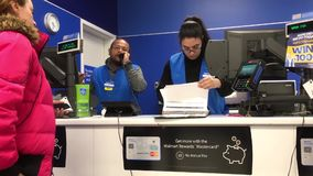Motion of people asking about lost item and worker checking lost log at customer service counter