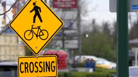 Motion of people and bicycle crossing sign on sidewalk with blur traffic flow. In BC Canada stock footage
