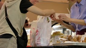 Motion of people buying bread and paying cash stock footage