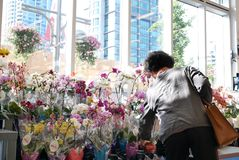 Motion of of people buying orchid on display flower rack inside price smart foods store Stock Photography
