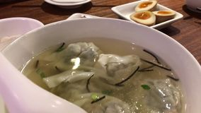 Motion of people eating dumpling soup and appetizers on table inside Chinese restaurant. In Taipei Taiwan stock video