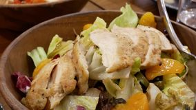 Motion of people eating grilled chicken citrus salad on table. Inside Japanese restaurant stock video footage
