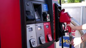 Motion of people filling up car gas tank with fuel stock footage