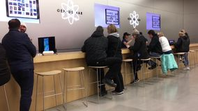 Motion of people having some service at genius bar inside Apple store